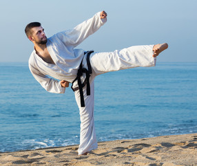 Man doing karate at ocean