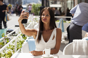Beautiful brunette dress taking pictures of herself on a cellphone