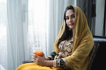 Muslim woman in yellow dress taking selfie.