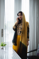 Muslim woman with mobile phone in the room.