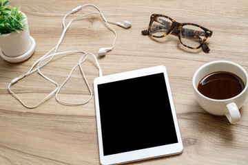 Top view workspace  on wooden desk with tablet, earphones, glasses and a cup of coffee.