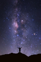 Milky way galaxy with stars and space dust in the universeand and silhouette of a standing happy man
