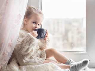 A little girl in the white knitted sweater sits on a window and drinks from a cup