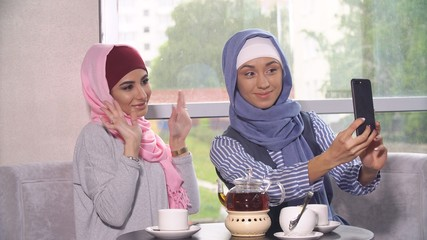 Two young women in hijabs do selfie on a smartphone. Muslim women in a cafe.