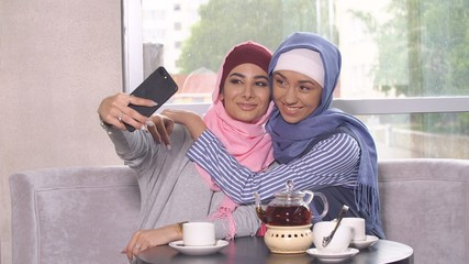 Beautiful Young Muslim Girls do selfie on a smartphone