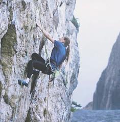 adult woman rock climber. rock climber climbs on a rocky wall. man makes hard move