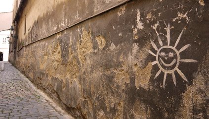 Street art stock image. Cracked wall in city. The sun on the wall. Graffiti wall with smile Sun