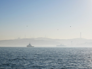 Foggy morning scenery of Istanbul's Bosphorus strait in Turkey. The canal divides Istanbul into Asia part and Europe part, and is a famous tourist spot to take cruise along the canal.