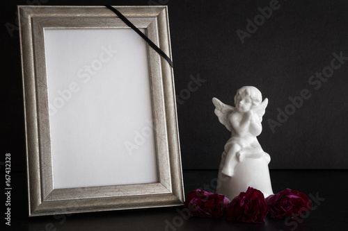 White blank condolence card with frame and white angel figurine on ...