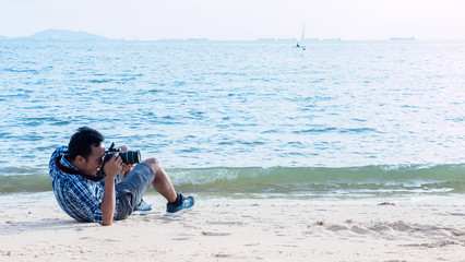 Young man half sitting and laying down on the ground on the beach holding a camera shooting a picture, happy moment for vactaion or leisure
