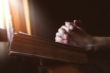Hands Praying on Holy Bible beside a Window Light, Hope and Religion Concept