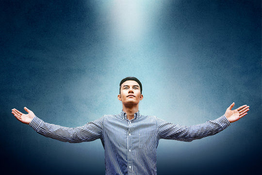 Freedom and Powerful Success Concept, Confident Man with Wide Open Arms and Looking up Light Above