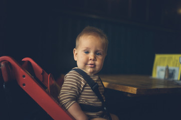 Baby on booster chair in cafe