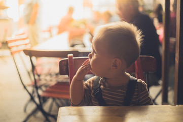 Little baby sitting at table in cafe