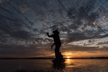 Silhouette of Fishermen throwing net fishing in sunset time at Wanon Niwat district Sakon Nakhon Northeast Thailand.