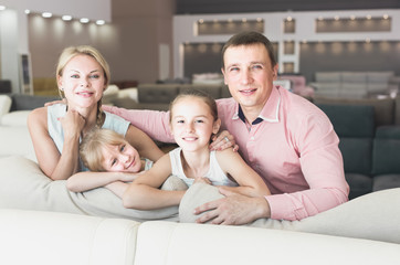 Wife with husband and kids are pleased by new sofa