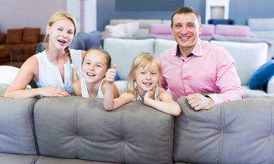Family are choosing new sofa in furniture store.