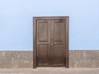 Braune Haustür aus Holz in einer blauen Fassade