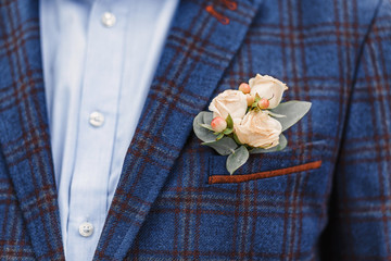 Groom with a wedding boutonniere in a checkered suit