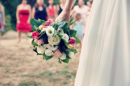 Gros plan d'une mariée en robe de mariage tenant un bouquet de fleurs devant les demoiselles d'honneur