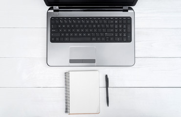 Wooden white office desk table with open blank laptop computer and empty white diary with pen, free space. Top view with copy space. Grey laptop on wooden background