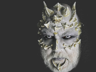 man or monster with thorns on face with futuristic makeup