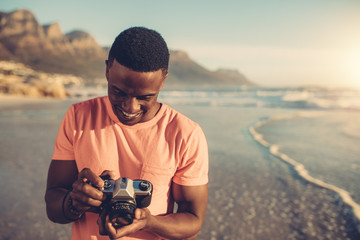 Young man checking photos in digital camera