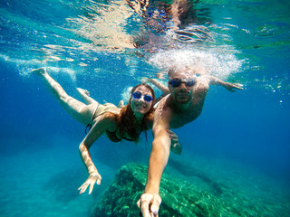 Joyful happy couple having fun underwater with selfie stick.