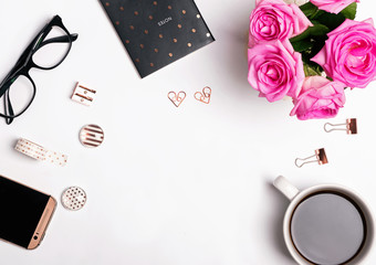 Pink roses, coffee and gold color accessories on the whit background.