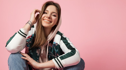 Portrait of a fashionable beautiful laughing girl in a sports jacket print and jeans sitting on a pink background