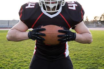 Facelessshot of man in football uniform and helmet holding ball.