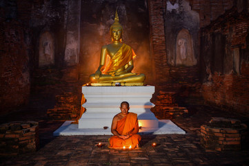 Buddhist Asian monk meditating under Bhudda in temple on during sunset,Thailand