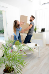 happy young couple student roommate packing boxes and moving furnitures during their move into new home flat apartment