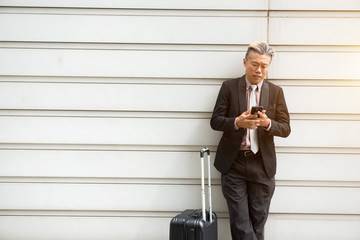 asian senior businessman travel with phone