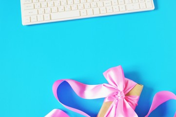 Online gift delivery/ White computer keyboard and gift box with pink bow on a blue background. Online order presents concept. Free space for text, mockup for design. Flat lay stock photography
