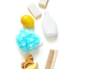 Soap and shampoo/ Baby soap, blue sponge puff, lemon fruit, shampoo bottle, wooden horse toy, comb on a white background. Free space for text. Mockup for design
