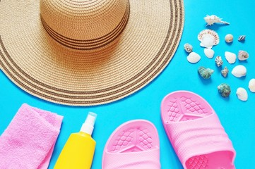 Flat lay beach background/ Straw hat, pink towel, yellow sunscreen bottle, slippers, seashells on a blue background. Flat lay beach background. Summer holiday concept
