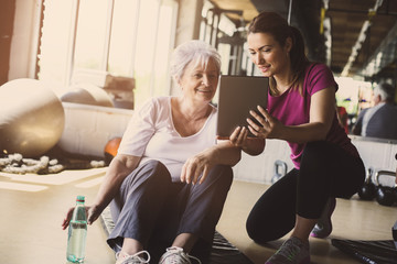 Senior woman workout in rehabilitation center. Personal trainer showing something  on digital tablet.