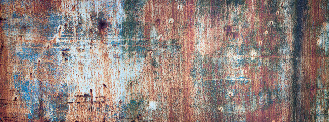 Rusty metal sheet background, rust with peeling multicolored paint