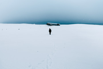 Person walking to the plane wreck in Iceland in the snow during winter