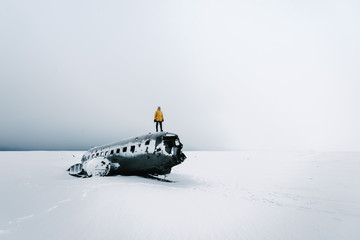 Person in yellow jacket standing on top of a plane wreck in Iceland during winter