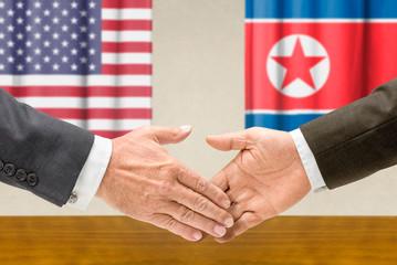 Vertreter der USA und Nordkoreas reichen sich die Hand