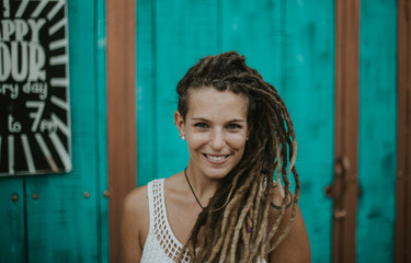 Portrait of young woman with dreadlocks posing outdoors