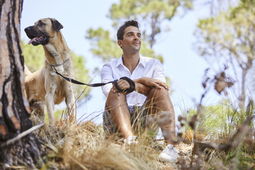 Guy relaxing in park with dog, smiling