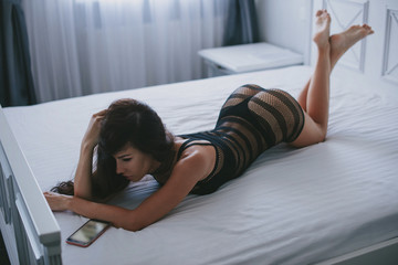 sexy young woman in black lingerie using a smartphone while lying on bed