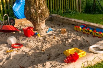 Sandkasten mit Spielsachen unter einem Baum