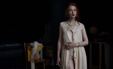 Girl in vintage style is retro in unbuttoned dress on the stage of the abandoned theater