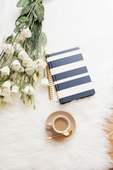 Notebook, tablet, a cup of coffee and a large bouquet white flowers on the floor on a white fur carpet. Freelance fashion comfortable femininity home workspace in flat lay style.