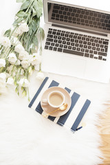 Notebook, laptop, a cup of coffee and a large bouquet white flowers on the floor on a white fur carpet. Freelance fashion comfortable femininity home workspace in flat lay style. T