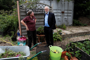 Britain's opposition Labour Party leader Jeremy Corbyn stands in the garden with Steph Perry at the Olive Tree Cafe in Swindon